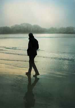 Mark Owen SILOUETTED MAN WALKING ON BEACH Men