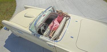 Terry Bidgood WOMAN LYING IN VINTAGE CAR Women