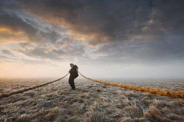 Leszek Paradowski MAN PULLING ROPES IN FIELD Men