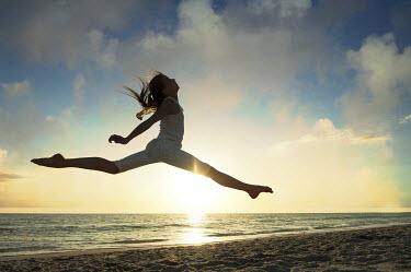 Terry Bidgood GIRL JUMPING ON SUNLIT BEACH Children