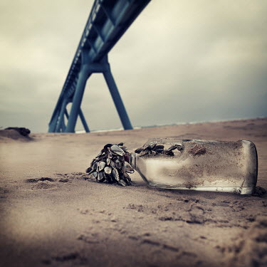 Christine Amat BOTTLE ON BEACH WITH PIER Seascapes/Beaches