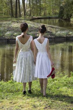 Yolande de Kort TWO GIRLS STANDING BY RIVER Women