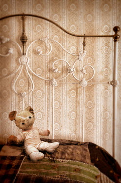 Jill Battaglia WORN TEDDY ON ANTIQUE BRASS BED Miscellaneous Objects