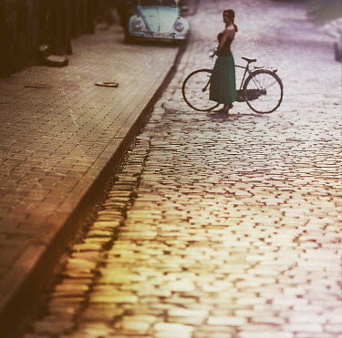 Marta Syrko WOMAN WITH BICYCLE ON COBBLED STREET Women