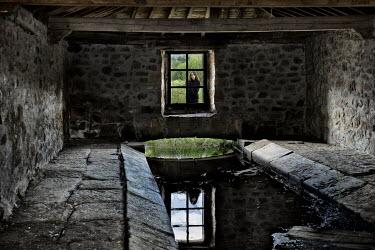 Fernando Arias Ramos WOMAN LOOKING INTO FARM BUILDING WINDOW Interiors/Rooms