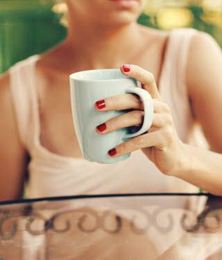 Irene Lamprakou WOMAN HOLDING COFFEE MUG IN GARDEN Women