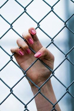 Elisabeth Ansley GIRLS HAND ON CHAIN-LINK FENCE Women