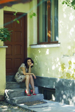 Veronica Gradinariu WOMAN SITTING ON STEP IN SUNLIGHT Women