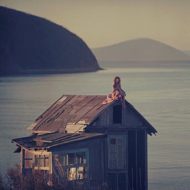 Oleg Oprisco WOMAN SITTING ON ROOF BY LAKE Women