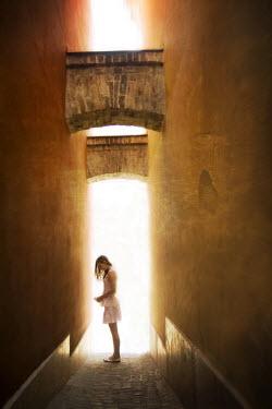 Hanna Nemeth GIRL STANDING IN SUNLIT ALLEYWAY Women
