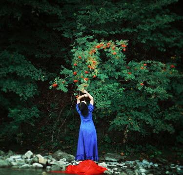 Raluca Deca WOMAN BY STREAM REACHING UP TO TREE Women