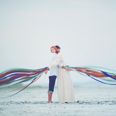 Oleg Oprisco COUPLE EMBRACING ON BEACH WITH RIBBONS Couples