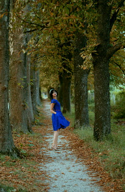 Muna Nazak WOMAN WALKING ON TREE LINED PATH Women