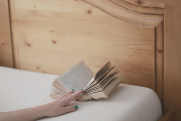 Karin Lips FEMALE HAND WITH BOOK ON BED Women