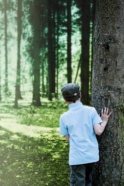 Yolande de Kort BOY PEERING ROUND TREE IN FOREST Men