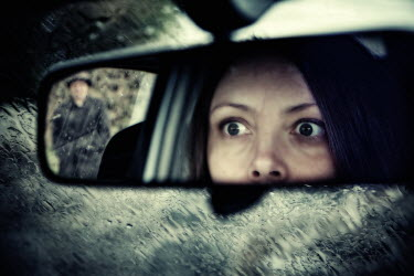 Dave Curtis WOMAN LOOKING IN REAR VIEW MIRROR, SINISTER MAN BEHIND Groups/Crowds