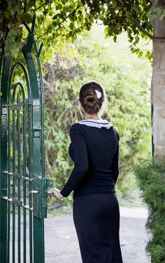 Ayal Ardon WOMAN STANDING AT GARDEN GATE Women