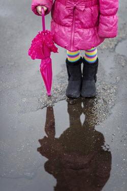 Karina Simonsen LITTLE GIRL BY PUDDLE WITH UMBRELLA Children
