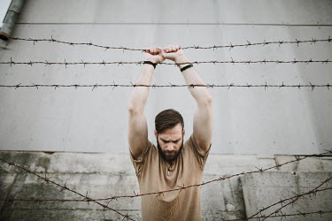 Sanja Kulusic MAN STANDING BY BARBED WIRE FENCE Men