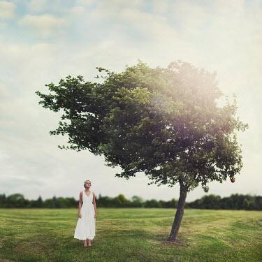 Vanessa Paxton WOMAN STANDING IN FIELD UNDER TREE Women
