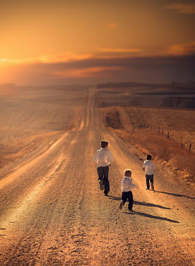 Jake Olson THREE BOYS PLAYING ON ROAD AT SUNSET Groups/Crowds