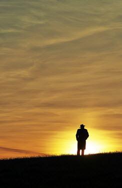 John Herbert Harrison SILHOUETTE OF MAN IN HAT AT SUNSET Men