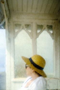 Nic Skerten WOMAN IN HAT IN BEACH SHELTER Women