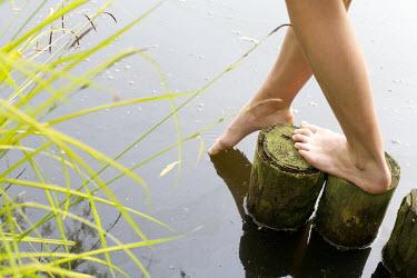 James Walker WOMAN STANDING ON POSTS IN WATER Women