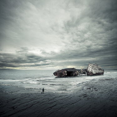 Christophe Dessaigne MAN ON BEACH WITH SHIPWRECK Boats