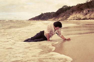 Wojciech Zwolinski MAN LYING IN WATER ON BEACH Men