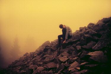 Jonas Hafner MAN SITTING ON PILE OF ROCKS Men