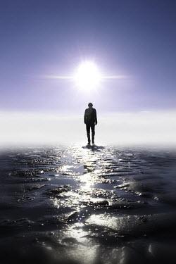 Tim Robinson SILHOUETTE OF MAN WALKING ON WET SAND Men
