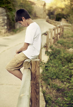Maria Jose Rivera TEENAGE BOY SITTING ON FENCE Children