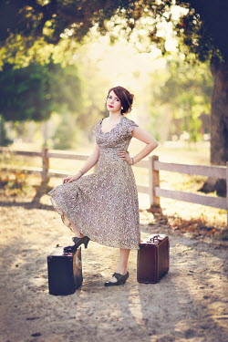 Jessica Drossin YOUNG BRUNETTE WOMAN WITH SUITCASES Women