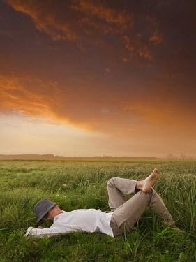 Leszek Paradowski MAN SLEEPING IN FIELD AT SUNSET Men