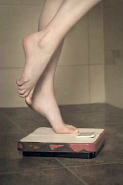 Emma Goulder WOMAN STANDING ON BATHROOM SCALES Women
