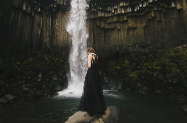 Whitney Justesen WOMAN IN DRESS AT FOOT OF WATERFALL Women