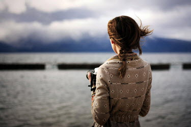 Whitney Justesen WOMAN WITH CAMERA BY WATER Women