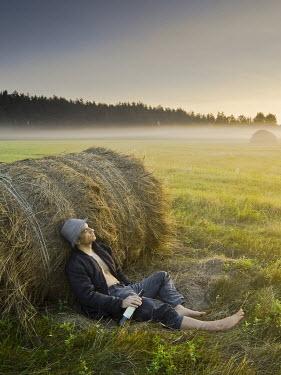 Leszek Paradowski MAN SLEEPING AGAINST HAY BALE Men