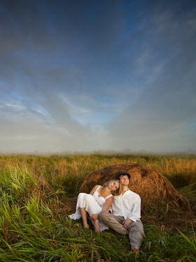 Leszek Paradowski COUPLE SLEEPING AGAINST HAY BALE Couples