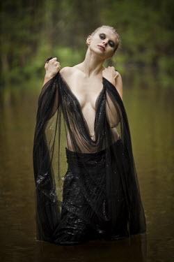 Leszek Paradowski WOMAN WITH NET STANDING IN WATER Women