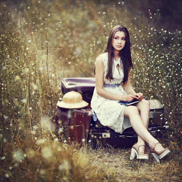 Natalia Ciobanu GIRL SITTING ON SUITCASES IN FIELD Women