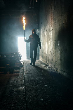 Stephen Carroll SILHOUETTE OF MAN WITH FLARE IN WAREHOUSE Men