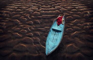 Kylli Sparre WOMAN IN BOAT ON WET SAND Women