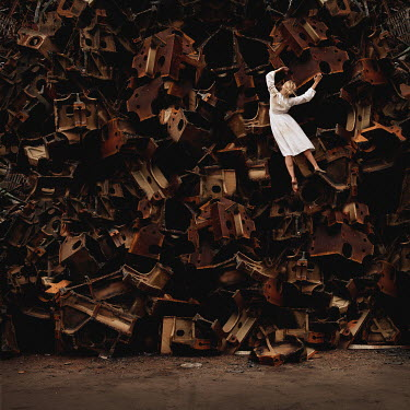 Kylli Sparre WOMAN BY PILE OF RUSTY METAL PARTS Women