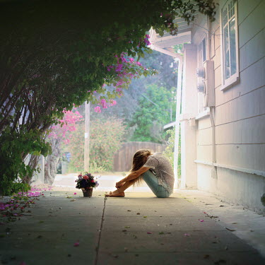 Paige Nelson GIRL SITTING BY HOUSE WITH FLOWERS Children