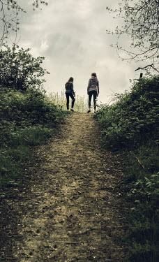 Stephen Mulcahey TWO TEENAGE GIRLS WALKING THROUGH A WOOD Children