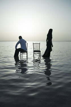 Nilufer Barin COUPLE WITH CHAIRS IN WATER AT DUSK Couples