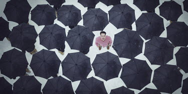 Logan Zillmer MAN STANDING AMONG UMBRELLAS FROM ABOVE Men