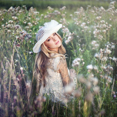 Lauren Alexandra Miller WOMAN IN WHITE HAT SITTING IN FLORAL MEADOW Women